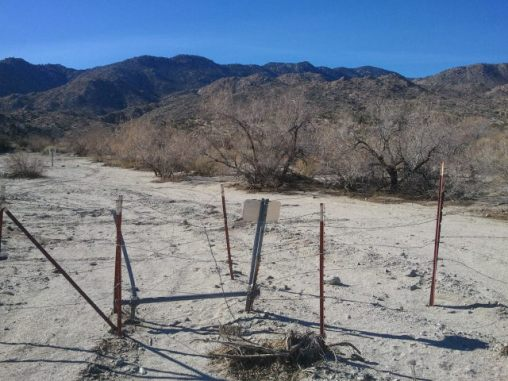 The fence at the mouth of the canyon, turn right immediately after this fence and stay in the wash (mile 7.08 in the race).